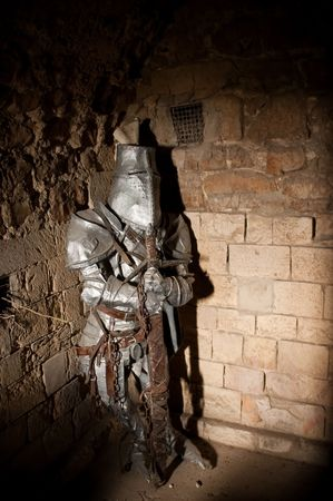 ancient prison: imprisoned medieval knight lit by a shaft of light Stock Photo