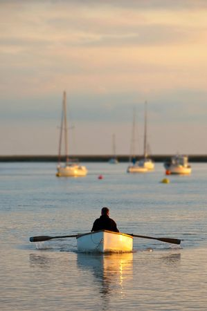 rowing boat: rowing into the sunset in a small wooden boat