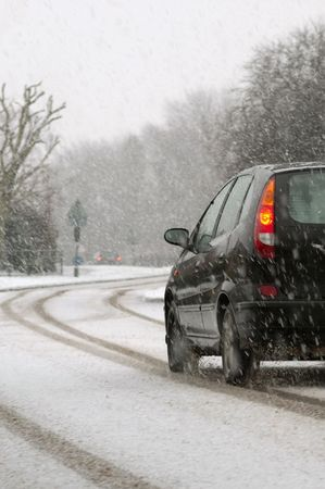 road conditions: vehicle traveling on a highway during snowfall Stock Photo
