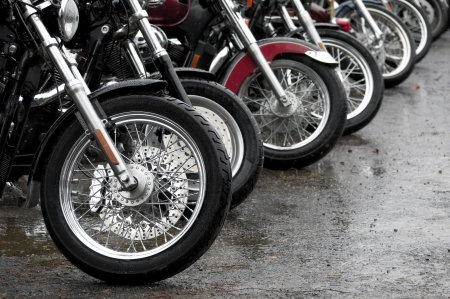 row of motorcycles parked together on a rainy day photo
