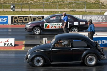 SANTA POD, UK - APRIL 23, 2010: Alternative energy racing at Santa Pod Raceway. Regular petrol VW Beetle and a vegetable oil powered Vauxhall Omega going head to head.