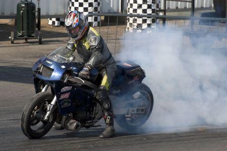 gilbert: SANTA POD, UK - APRIL 23, 2010: Alternative energy racing at Santa Pod Raceway. A burnout by Andy Gilbert on his 150 mph biofuel powered Suzuki motorcycle. April 23, 2010, Santa Pod, UK. Editorial