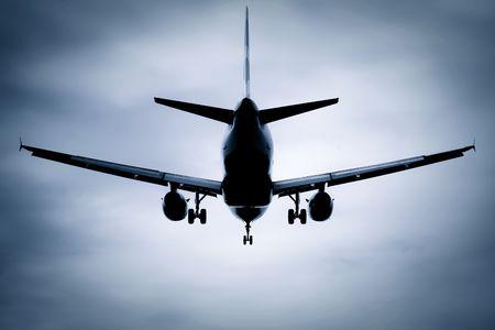 wingspan: silhouette passenger jet on takeoff or landing through soft focus clouds