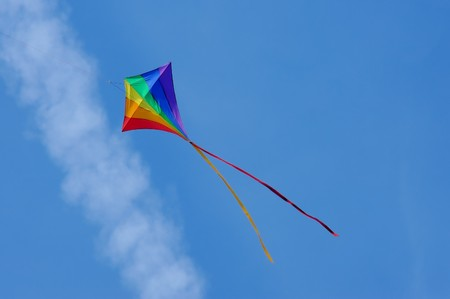 flying a kite: rainbow colored kite flying below an aircraft vapor trail Stock Photo