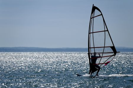 adrenaline rush: windsurfer silhouette against a sparking blue sea Stock Photo