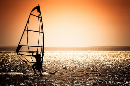 windsurfer silhouette against a sunset background Stock Photo