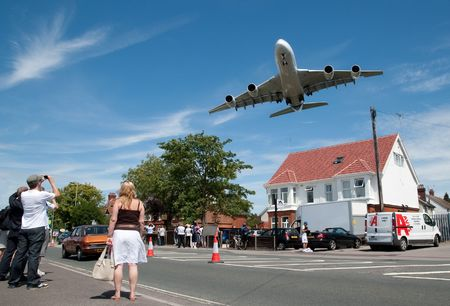 Farnborough International Airshow, UK - July 19, 2010: Massive Airbus A380 aircraft on landing approach over a local suburban street.