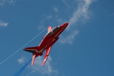 Farnborough International Airshow, UK - July 15, 2010: Banking maneuver by a Red Arrows aerobatic display jet during pre-show practice.