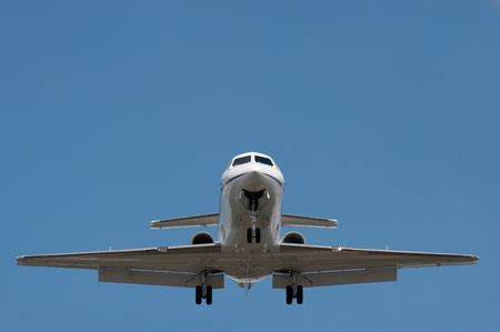 jets: business jet on landing approach against a clear blue sky