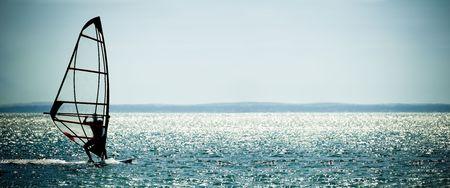 wind surf: windsurfista panorama silueta contra un provocando azul mar