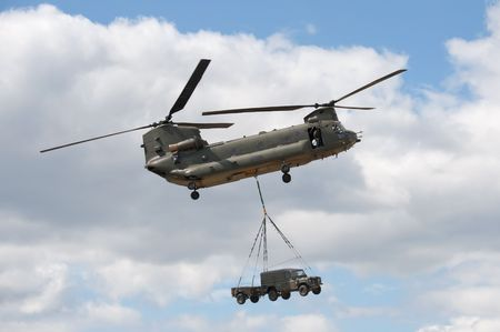 FARNBOROUGH AIRSHOW, UK - JULY 24, 2010: RAF Chinook helicopter in heavy vehicle lift demonstration.