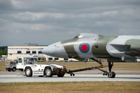 towed: FARNBOROUGH AIRSHOW, UK - JULY 24, 2010: Avro Vulcan XH558 towed by an airfield tug truck due to brake failure.