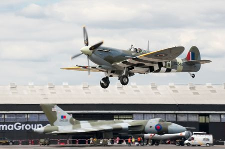 ww2: FARNBOROUGH AIRSHOW, UK - JULY 24, 2010: WW2 Spitfire coming into land with XH558 Vulcan bomber in the background.