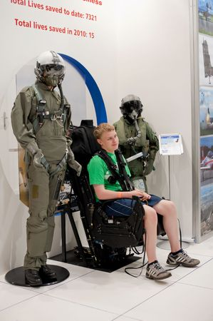 ejector: FARNBOROUGH AIRSHOW, UK - JULY 25, 2010: Teenager straped into the latest Martin-Baker aviation ejection seat.