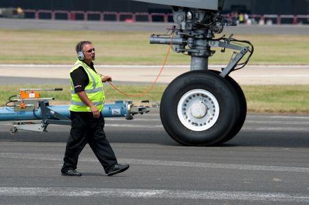 transporte terrestre: Exhibición de vuelo de FARNBOROUGH, Reino Unido - 25 de julio de 2010: ingeniero de la tripulación de tierra con la responsabilidad de dirigir un avión Airbus A380 en su posición de visualización.  Editorial