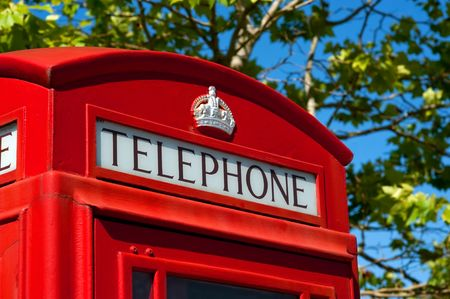 payphone: traditional british red telephone call box with a leafy background