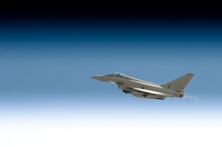 military fighter jet powering through a gradient blue sky photo