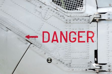 danger sign on the side of a riveted aircraft fuselage photo