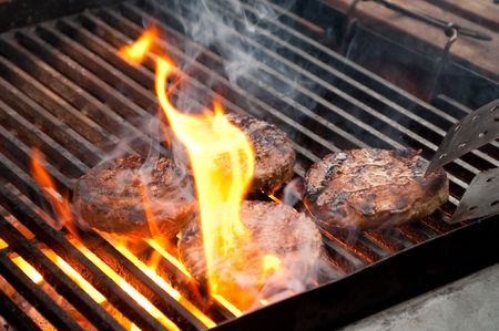 tasty burgers being cooked on a flaming barbecue photo