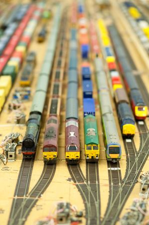 collection of model trains in an unfinished miniature goods yard