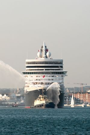 SOUTHAMPTON, UK - OCT 12, 2010: Hazy sunset departure from port for the Queen Elizabeth ocean cruise liner on her maiden voyage.