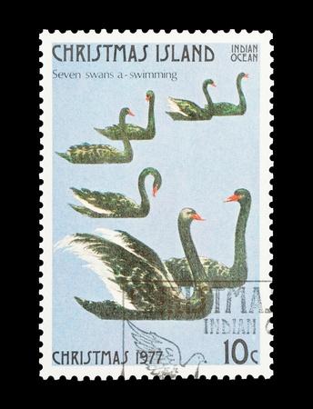 cisnes: Sello de correo de la isla de Navidad con el regalo s�ptimo de los doce d�as de Navidad Foto de archivo