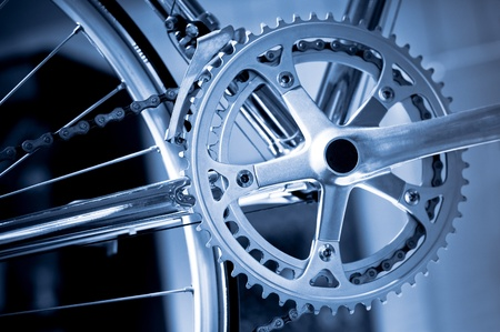 'cycles: chromed precision racing bike gearwheels and chain with a blue tint