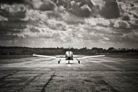 airfield: sepia toned propeller aircraft taking off into turbulent looking clouds Stock Photo