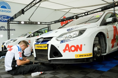aon: Thruxton, United Kingdom - May 1, 2011: Engineer working on the Team Aon Ford Focus belonging to driver Tom Chiltern at the Thruxton BTCC race meeting, UK.