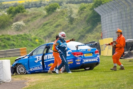 Thruxton, United Kingdom - May 1, 2011: Jason Plato, reigning British Touring Car champion being helped by track marshalls after crashing his Silverline Chevrolet during a race at Thruxton, UK. Stock Photo - 9444792