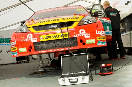 Thruxton, United Kingdom - May 1, 2011: Mechanic working on the Airwaves Ford Focus belonging to driver Liam Griffin in the British Touring Car Championship at  Thruxton, UK Stock Photo - 9472275