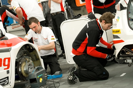 Thruxton, United Kingdom - May 1, 2011: Mechanics from the Honda team working on the race winning Civics at the British Touring Car Championship in Thruxton, UK Stock Photo - 9472284