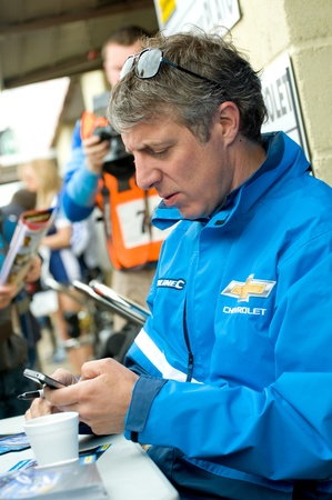 reigning: Thruxton, United Kingdom - May 1, 2011: Jason Plato, reigning British Touring Car champion sending a text message during autograph signings at  the race meeting in Thruxton, UK. May 1,