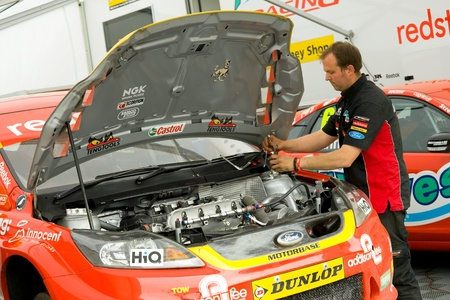 toca: Thruxton, United Kingdom - May 1, 2011: Airwaves team mechanic working on the Ford Focus belonging to driver Mat Jackson at the British Touring Car Championship at Thruxton, UK