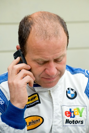 Thruxton, United Kingdom - May 1, 2011: British Touring Car Championship driver Rob Collard recieving a call during a race meeting at Thruxton, UK Stock Photo - 9472206