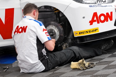 Thruxton, United Kingdom - May 1, 2011: Team Aon mechanic working on the Ford Focus driven by Tom Chiltern at the British Touring Car Championships, Thruxton, UK Stock Photo - 9472265