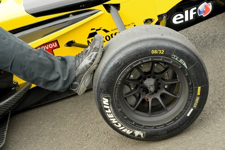 Thruxton, United Kingdom - May 1, 2011: Mechanics foot helping to move a race car at the Formula Renault championship meeting in Thruxton, UK Stock Photo - 9472189