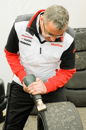btcc: Thruxton, United Kingdom - May 1, 2011: Honda Racing mechanic removing blisters with a hot iron on race tires during the British Touring Car Championships at Thruxton, UK