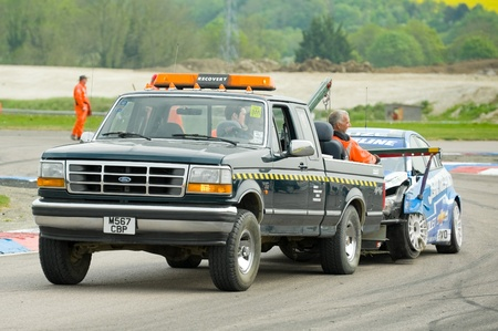 toca: Thruxton, United Kingdom - May 1, 2011: Recovery truck towing away wreckage of a Chevrolet driven by Jason Plato during the British Touring Car Championships, Thruxton, UK Editorial