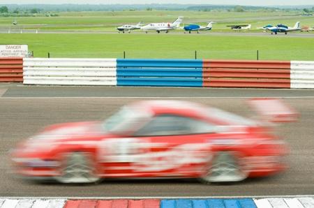 btcc: Thruxton, Regno Unito - 1 maggio 2011: Motion blur di una macchina da corsa in un evento Porsche Carrera Cup il 1 maggio 2011 a Thruxton, Regno Unito.