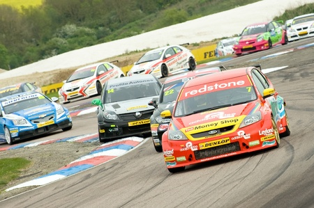 Thruxton, United Kingdom - May 1, 2011: Airwaves Ford Focus driven by Mat Jackson leading a large pack of cars in the British Touring Car Championships on May 1, 2011 in Thruxton, UK.