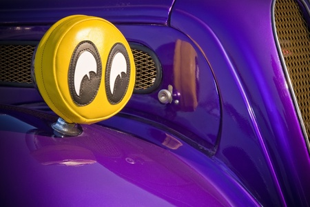 purple car: humorous big eyes covering the headlights of a purple car