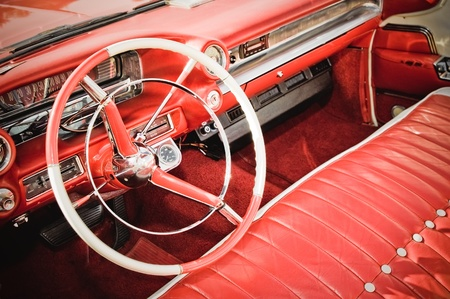 retro styled classic car interior with red leather upholstery and matching dashboard