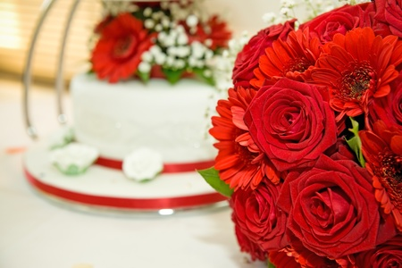 red wedding flowers with wedding cake in the background