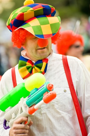 watergun: Upper Hale, UK  - July 2, 2011: Colorful clown with a water gun in a carnival procession.
