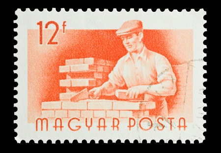 bricklayer: Mail stamp printed in Hungary featuring a bricklayer at work, circa 1955 Editorial