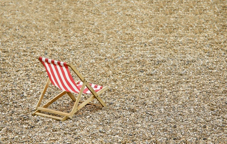 Pebble Beach: single deck chair on a deserted pebbled beach Stock Photo