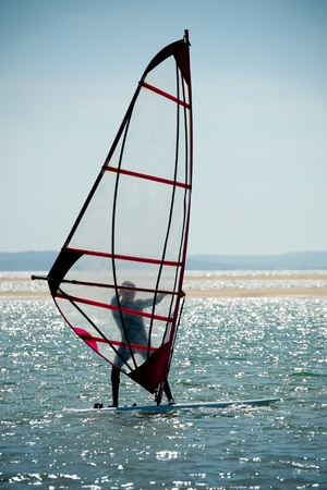 sparking: windsurfer silhouette against a sparking blue sea Stock Photo