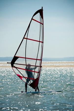 windsurfers: windsurfer silhouette against a sparking blue sea Stock Photo