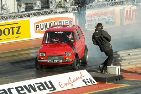 Santa Pod Raceway, UK - Oct 29, 2011: Modified small Fiat dragster losing control during a burnout at the Flame and Thunder racing event.